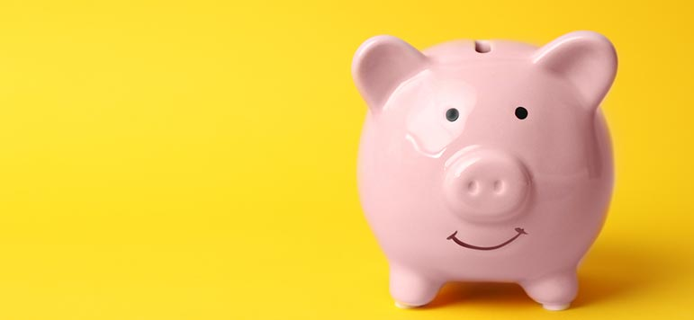 Pink piggy bank on yellow background